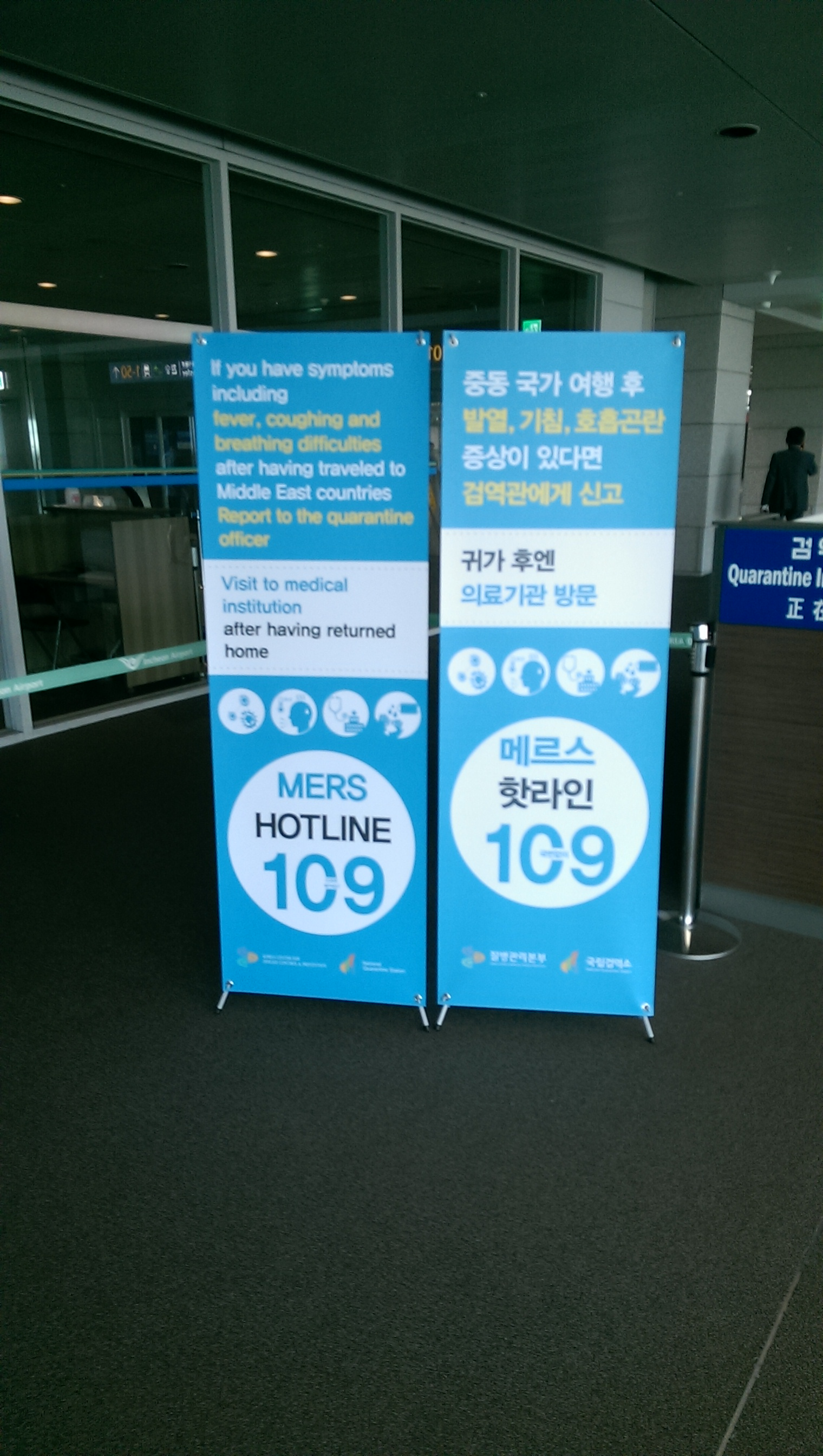 [Signs informing travelers about MERS in English and Korean]