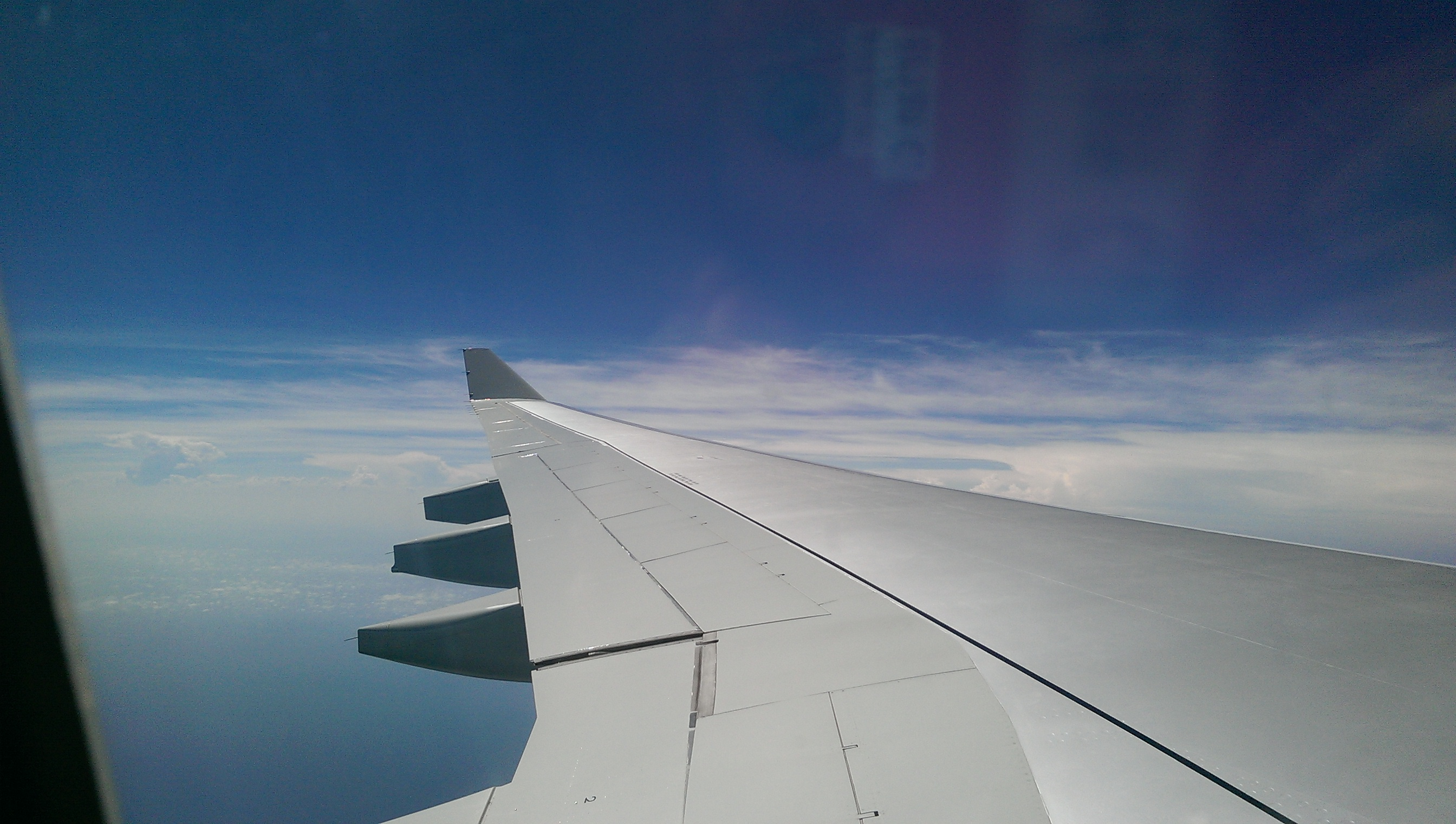 [View of airplane wing and clouds from airplane]